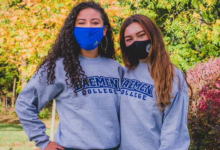 Two female students in masks wearing Daemen sweatshirts outside