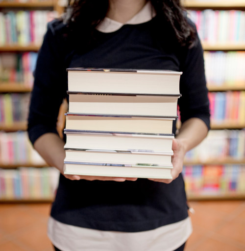 Female holding a stack of books with shelves of books in the distance