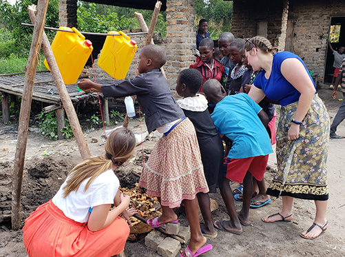 Social Work students helping kids in an African village setup a hand washing station