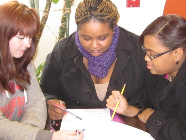 Three students sitting at a table for coaching session
