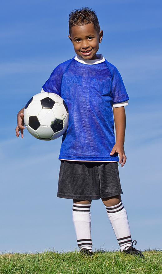 Adolescent boy in soccer uniform holding a soccer ball