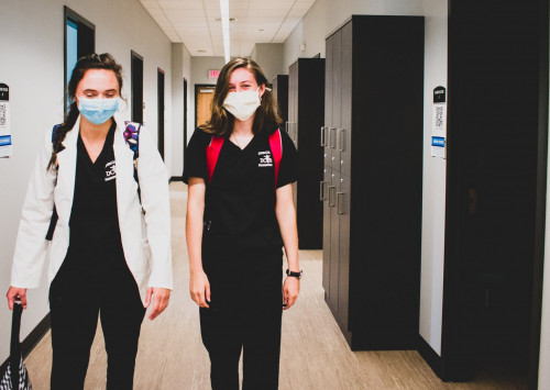 Two female PA students walking down the CILS hallway