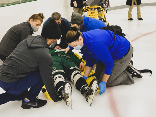 Athletic Training staff helping hockey player laying on the ice