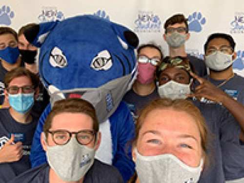 Students wearing face masks with willie the wildcat