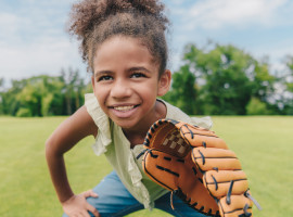 Adolescent girl holding a softball mitt playing in a field